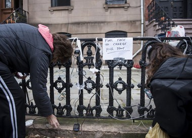 People pictured charging their cell phones outside a Hoboken home that did not lose power during Hurricane Sandy.