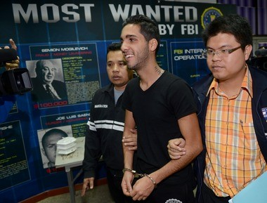 Hamza Bendelladj of Algeria, center, a suspect on the FBI's top-ten wanted list for allegedly hacking private accounts in 217 banks and financial companies worldwide, is escorted by Thai police officers during a press conference at the Immigration Police Bureau in Bangkok on January 7.