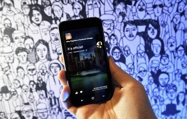 A Facebook employee displays an HTC phone with the new Home operating system against the backdrop of a decorated wall at Facebook's headquarters in Menlo Park, Calif. on Thursday.