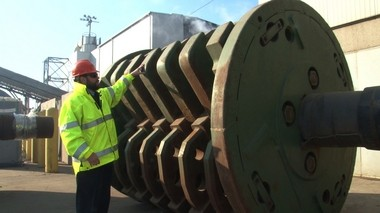 Daniel Strechay, a spokesman Sims Metal Management, stands next to a spare rotor from the company's mega shredder in Jersey City's Claremont Terminal.