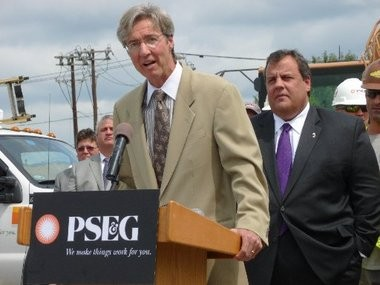 PSEG CEO Ralph Izzo peaks at a ribbon-cutting for a PSE&G solar farm on a brownfield in Hackensack as Gov. Chris Christie looks on in July 2012.