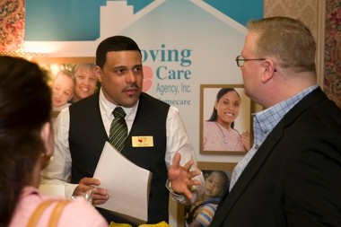 John Collazo, regional nurse recruiter at the Loving Care Agency talks with job seekers at a job fair held in Newark in April.