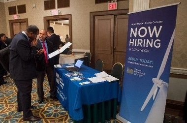 Applicants talk with potential employers at a job fair in New York last week. Unemployment rates are considerably higher in lower-income families.