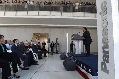Gov. Chris Christie addresses the crowd at Panasonic's grand opening of its new headquarters in Newark as employees watch from above.