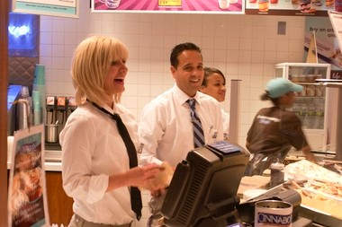 """Cinnabon president Kat Cole, left, wears a disguise and works behind the counter with store manager Miguel Di Costanzo during the taping of an episode for the CBS show """"Undercover Boss."""""""