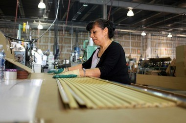 An employee inspects an extruded frame piece of foam-turned-moulding at Princeton Moulding in North Brunswick.