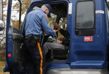 A New Jersey State trooper inspects a driver's paperwork during a sting operation to catch unlicensed movers.