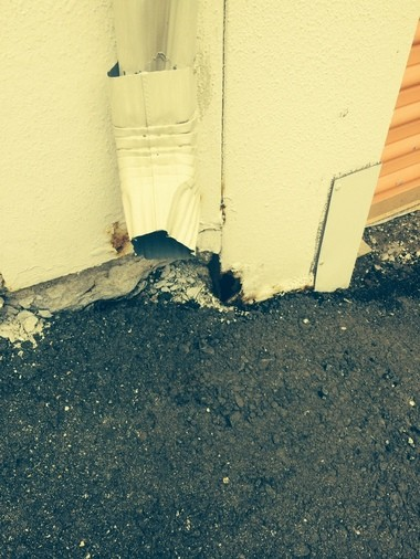 A photo of a downspout next to a hole in a Public Storage unit's wall.