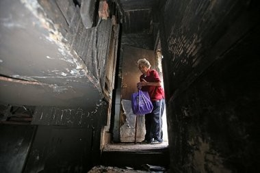 Gwendolyn Dixon looks into the basement of her fire-destroyed home.