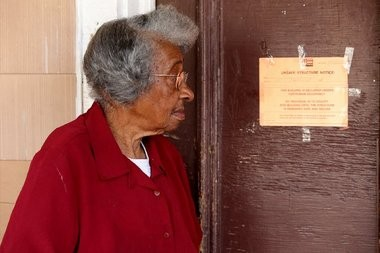 "Gwendolyn Dixon reads the ""unsafe structure notice"" on her front door."