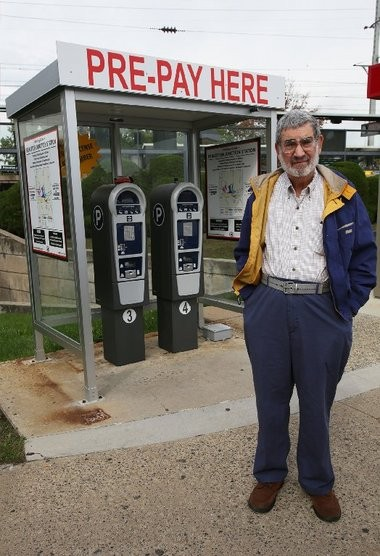 Larry Zisman stands with the parking kiosks at the West Windsor Parking Authority lot.