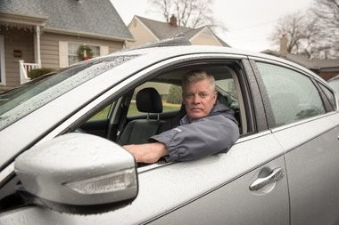 Ken Lowenstein sits in his car. He wants to know why his insurance credit score is low even though his traditional credit score is high.