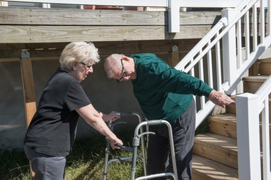 Gail Seckler braces herself and Don Seckler's walker as he gets up after going down his stairs on his bottom.