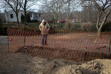 Karl Baer stands on his property, which was dug up by A.J. Perri to replace a sewer line.