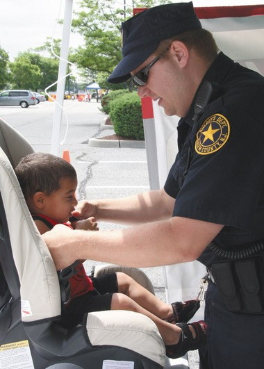 060609 Staff Photo by JESSE BAIR Officer Lauer fits eighteen month old, Kameron Brown into his new car seat. Car seat safety inspections were conducted as part of Community Safety Day in the Wal-Mart parking lot in Pennsville on Saturday.