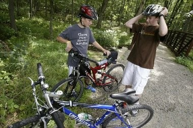Two Randolph boys put their helmets on before riding their bicycles in this file photo. A South Jersey town will reward children who are caught wearing helmets while riding.