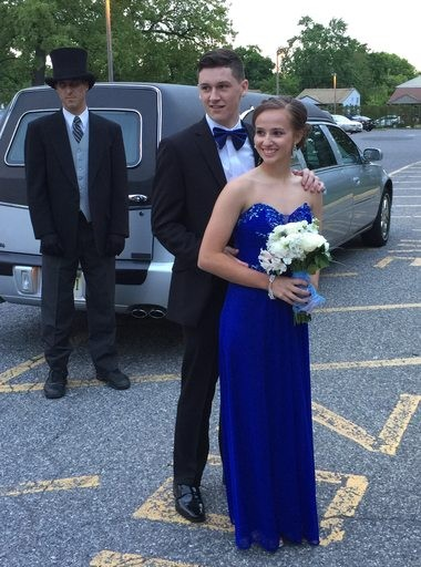 Megan Flaherty poses at the Pennsauken High School junior prom with her date, Stephen Caldwell, while her family friend and funeral director Dennis McGee, who drove the hearse, looks on May 6, 2017.
