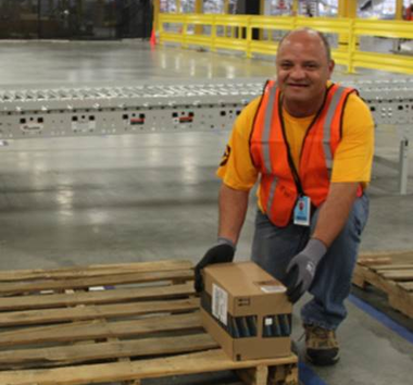 Amazon Employee Luis Rospigliosi gets the first item shipped ready to head out of the fulfillment center to a customer in New York.