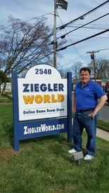 Charlie Ziegler with the ZieglerWorld's new location sign at 2540 Nottingham Way, Hamilton, NJ.