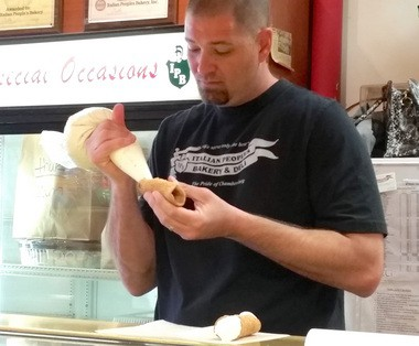 Matthew Guagliardo, the store manger at the main location in Trenton, fills a homemade shell with cannoli filling. (Shayna Innocenti photo)