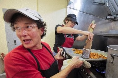 Abby Hoffman of South Brunswick (left), the unofficial kitchen manager on Fridays at Elijah's Promise soup kitchen, gives orders to a fellow volunteer as she helps Nancy Engel of Monroe add chopped sweet potatoes to a batch of risotto they are making for the afternoon meal.