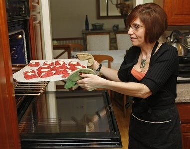 Serena Blackin takes a batch of red velvet hamantaschen out of the oven.
