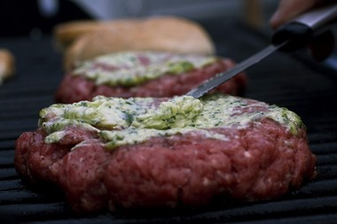 A shallot and parsley butter mixture is smeared onto the top of a grilling burger.