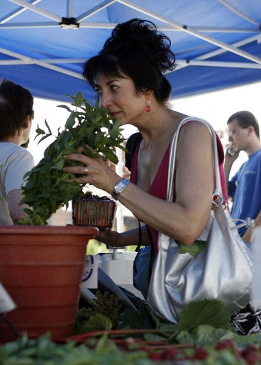 A customer smells fresh mint at a stand run by Alstede Farms from Chester.