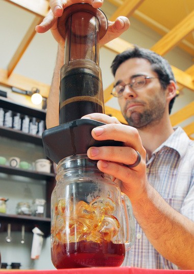 Ben Schellack uses an AeroPress to force hot water through grounds to make ice coffee using the Japanese method at OQ Coffee.