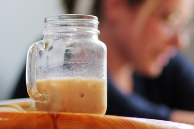 A customer sits with her iced coffee with dairy at OQ Coffee in Highland Park.