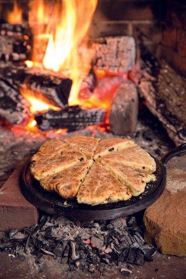 """Cream scones bake on a cast iron griddle over fireplace coals. Image from """"Cooking with Fire"""" by Paula Marcoux."""