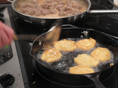 Chef Rachel Reuben turns potato pancakes frying in hot oil at a holiday appetizer class at Food Fix Kitchen in Lebanon Twp. Norwegian meatballs are in the background.