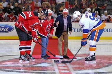 Devils owners David Blitzer, center left, and Josh Harris drop ceremonial pucks between Devils defenseman Bryce Salvador and Islanders center John Tavares at the Oct. 4 home opener at the Prudential Center.