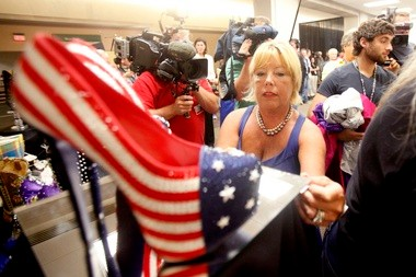 Fran McManus, a Miss America volunteer, helps with the shoe display, including the patriotic, oh-so-high stems that belong to Miss Pennsylvania.