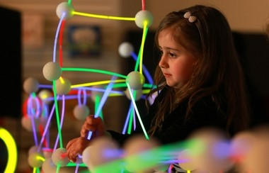 Kayla Rose builds a glow-in-the-dark structure using glowsticks and foam balls. Overdeck is using the activity to promote 'Bedtime Math' at bookstores across the country.