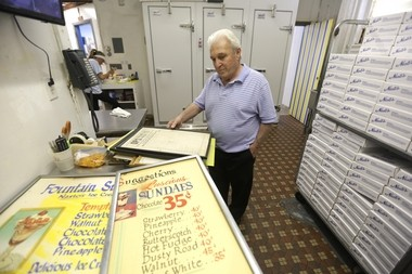 """Frank Nasto Jr. looks at old Nasto's menu signs -- """"luscious"""" chocolate sundaes once sold for 35 cents."""