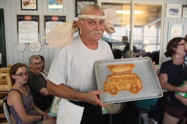 Bill Smith, owner and head chef of Mustache Bill's Diner, with his Munchmobile-shaped pancake.
