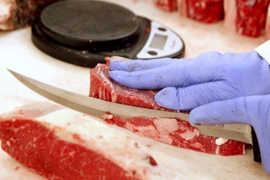 A butcher trims fat away from a steak at Pat LaFrieda Meat Purveyors