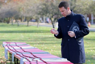 Philip Robertson, adjudicator from Guinness World Records, assesses a string of cranberries at Rider University. The school, founded by a 'cranberry king', broke the record for longest line of fruits this month. (Mary Iuvone/For The Times of Trenton)