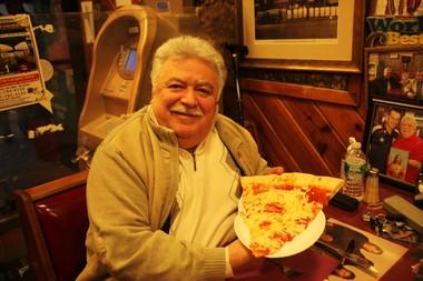 Benny, owner of Benny Tudinos pizzeria holds a massive slice of pizza, in Hoboken on Nov. 21, 2014.