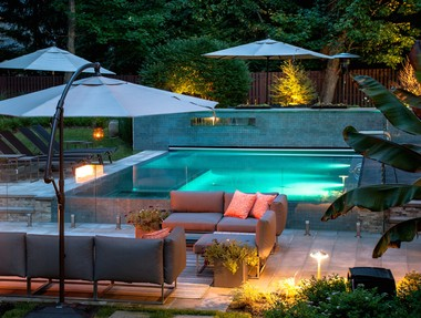 A pool in Upper Saddle River with infinity edges, glass tile and a fire feature. (Cipriano Landscape Design & Custom Swimming Pools)