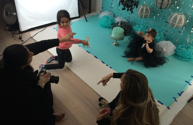 Photographer Harshita Malhotra, at left, tries to get 1-year-old Viviana D'Ippolito in a good mood for her 'cake smash' photo shoot. Malhotra's daughter, Avneet, 5, uses a squeaky toy to get the baby's attention as Viviana's mother, Heather, looks on. (Amy Kuperinsky | NJ Advance Media for NJ.com)