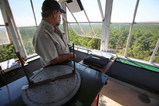New Jersey Forest Fire Service fire observer Craig Watson stands in the Apple Pie Hill fire tower alongside an Alidade, an instrument used to determine the location of any fires he spots Sept. 15, 2016 (Brian Donohue | NJ Advance Media for nj.com)