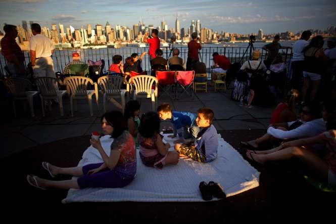 With the New York City skyline in the distance, people wait for the Macy's fireworks show to begin in Weehawken. (Photo by Yana Paskova/Getty Images)