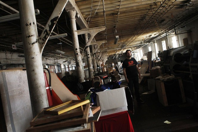 """John Ruggiero of New Jersey Paranormal in Paterson's Art Factory. The ghost-hunting group has investigated this cluttered room, nicknamed the """"beer garden,"""" due to claims by employees. On Saturday, the Art Factory, site of a former mill, will host the New Jersey Paraunity Expo, a gathering of ghost hunters, psychics and other paranormal professionals. (Frances Micklow 