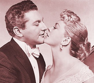 """Liberace and Dorothy Malone pucker up, almost, in """"Sincerely Yours."""""""