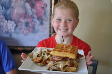 Holly Anthony holds up the chicken and waffles at Anthony's Cheesecake in Bloomfield.