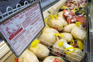 A freezer case of frozen turkeys.