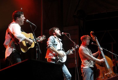 Mumford & Sons members Marcus Mumford, left, Winston Marshall and Ted Dwane play at Pier A in Hoboken in 2012.