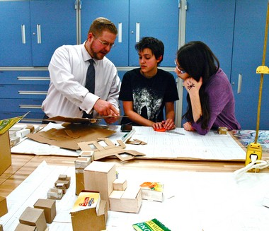 Livingston teacher Kenneth Zushma reviews a project with Heritage Middle School FemGineers Daria Collins and Ally Montalto.